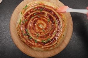 Аккуратно скручиваю рулетики со сливочным маслом, чесноком и орегано и выкладываю на сковородку: рецепт ароматного хлеба без духовки