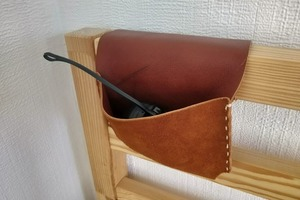 Сделали и закрепили в изголовье кровати подвесной кожаный карман: в нем очень удобно хранить телефон, книгу или другие вещи